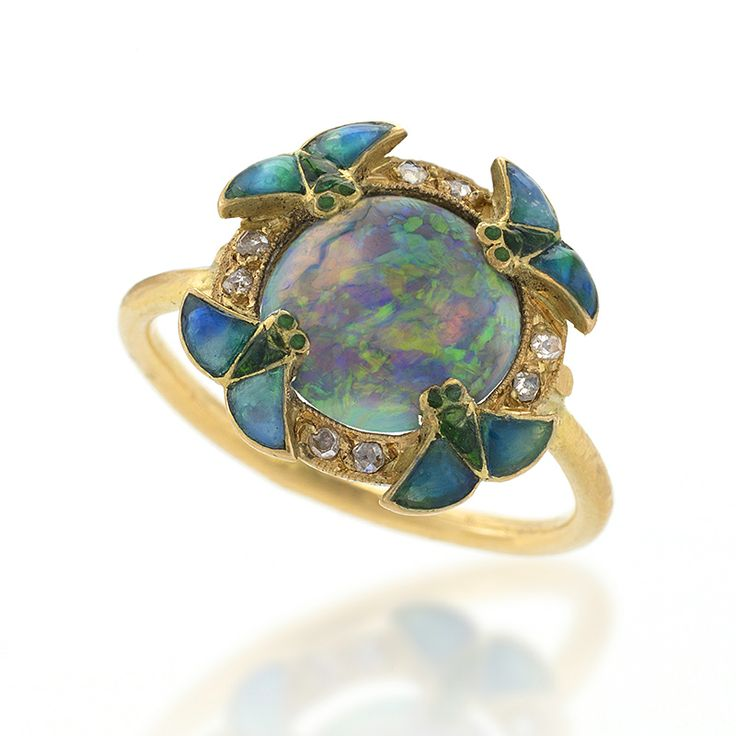 Eugene Feuillatre Art Nouveau Diamond, Opal, Gold and Enamel Ring. A French Art Nouveau 18 karat gold and enamel ring with opal and diamonds by Eugene Feuillatre. The ring has a center black opal, surrounded by 8 rose-cut diamonds and 4 enamel wings. The closed gallery is decorated with a gold/enamel scrollwork design.