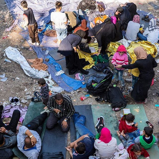 People rest at an intermediate camp at the junction of the village Sykamia in Lesbos. According to UNHCR, Lesbos has received 220,000 refugees and migrants during the first nine months of 2015. Which is 40% of the 575,000 total who have reached Europe this year. This is Dionysis Kouris @dionysiskouris, following refugees after they land on #lesbosisland in #greece . #humanrights #refugeeswelcome #opensociety #syrianrefugees  #refugees