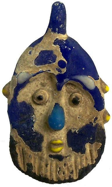 Ancient Phoenician. Blue fused glass face pendant with traces of yellow, light blue, black, and white features. 400-200 BC