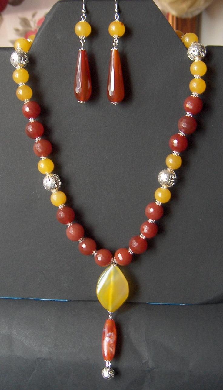 Collana montata su cavetto d'acciaio con boule di corniola sfaccettata 14 mm, agata gialla 10 mm ed elementi in filigrana