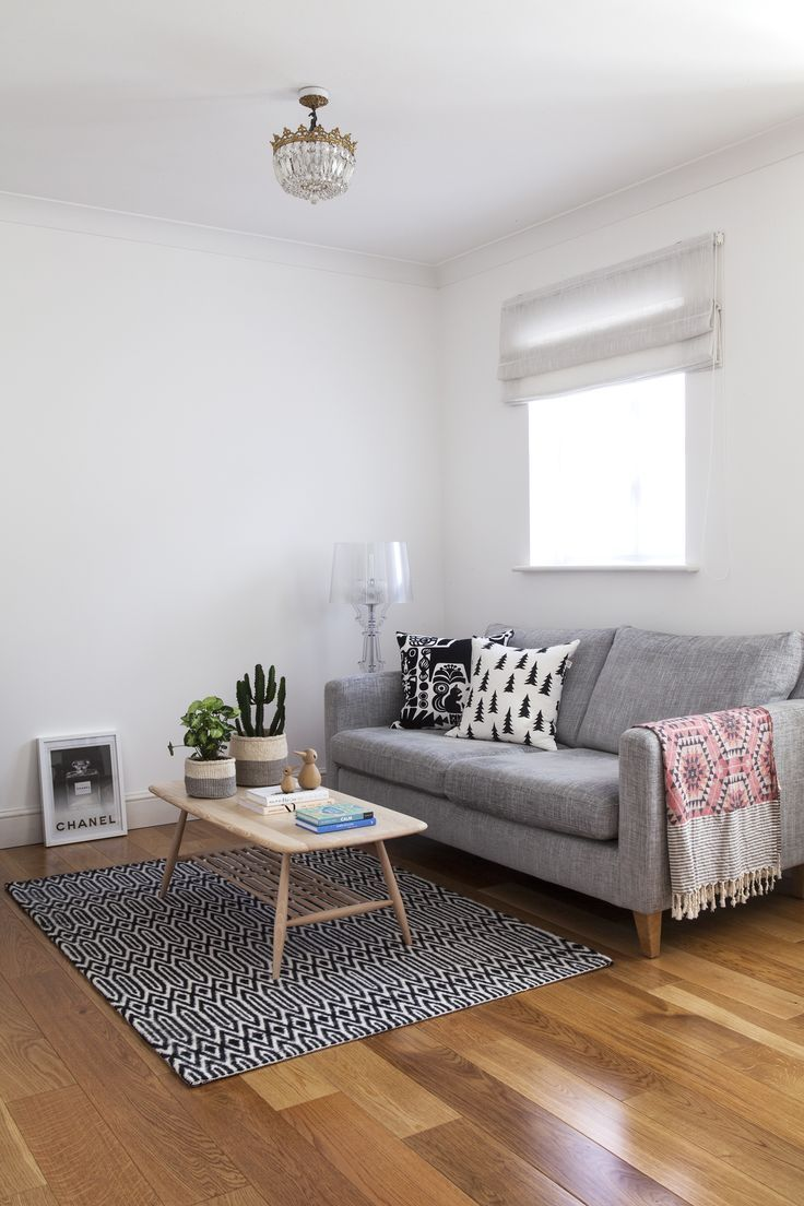 White living room with grey sofa and Ercol coffee table.