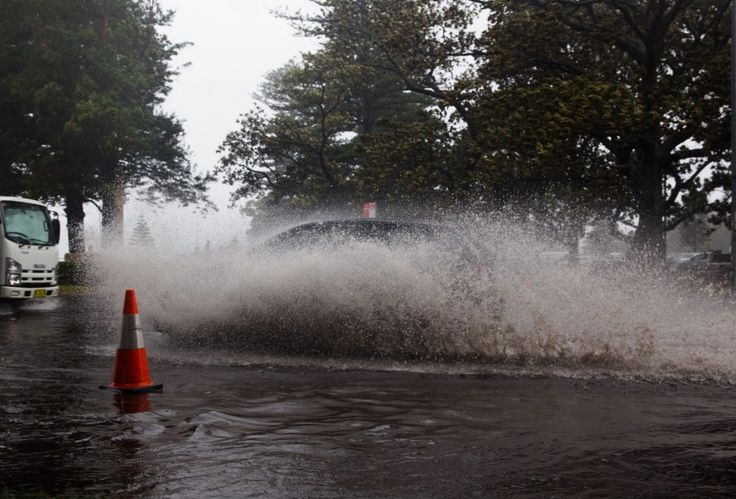 Motorists drive through the flood at New South Head Road in Rose Bay, Sydney.