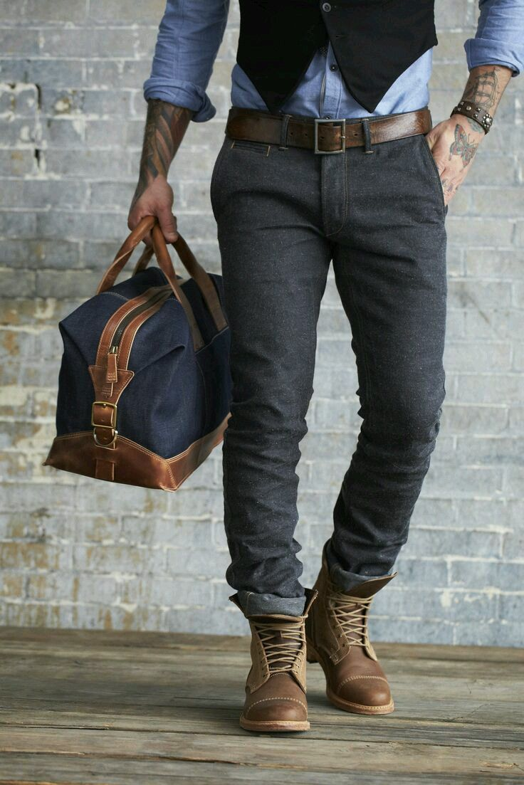 Shop this look on Lookastic:  https://lookastic.com/men/looks/waistcoat-long-sleeve-shirt-chinos/14347  — Black Waistcoat  — Light Blue Chambray Long Sleeve Shirt  — Dark Brown Leather Belt  — Charcoal Chinos  — Navy Canvas Duffle Bag  — Brown Leather Casual Boots