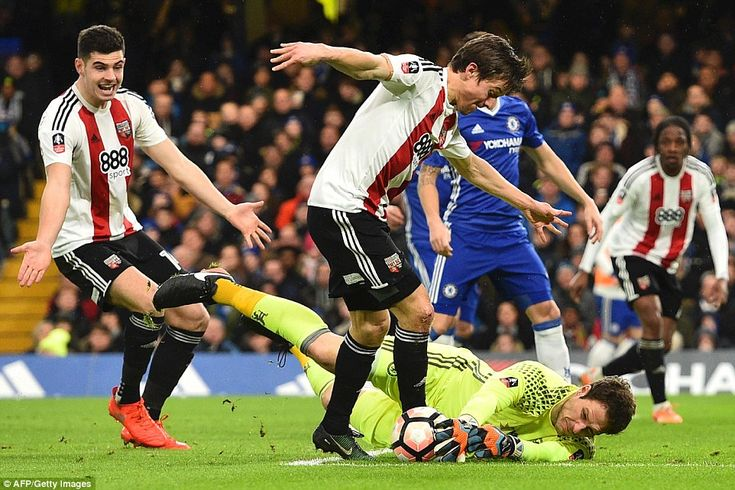 Chelsea keeper Asmir Begovic dives at the feet of Brentford's Lasse Vibe as team-mates wait for a pass in the middle