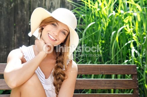 Stock Photo : Smiling young woman sitting on bench, portrait