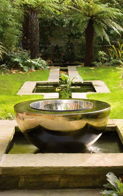 Chalice stainless steel water feature in garden setting David Harber