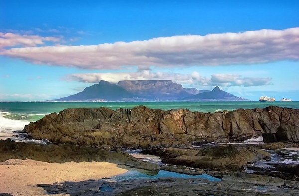 Table Mountain is a South African icon and the most recognized landmark of Cape Town. The flat-topped formation with peaks reaching 1,086 m above sea level has withstood six million years of erosion and is the only natural site on the planet to give name to a constellation of stars - Mensa...