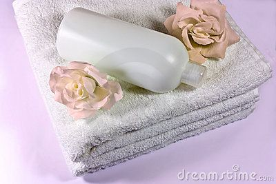 A closeup of soft towels, a bottle and silk roses