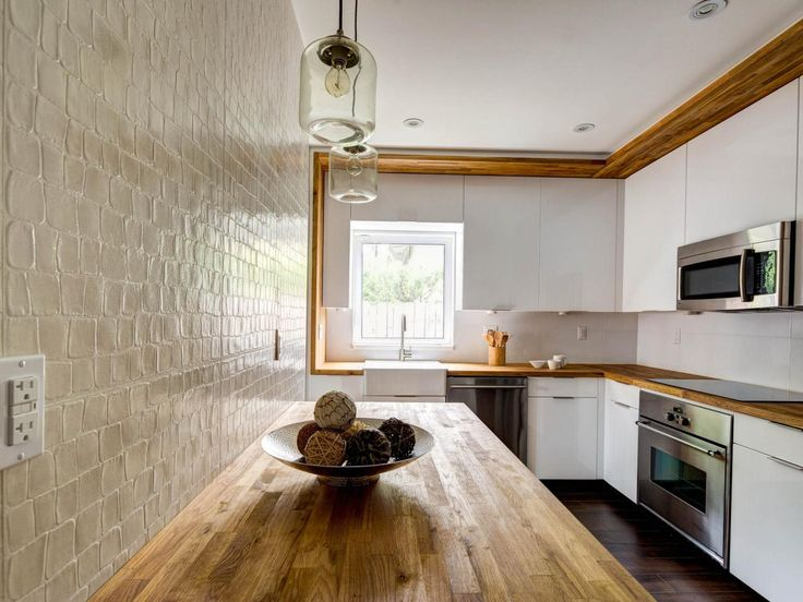 White Country Kitchen With Butcher Block butcher-block countertops give this modern white kitchen a warm