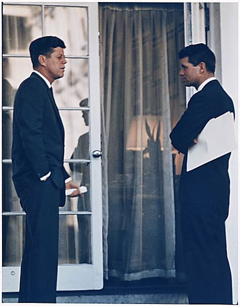 Kennedy speaking with his brother Attorney General Robert Kennedy at the White House, outside an Oval Office doorway.