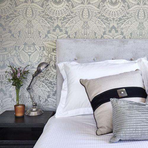 Master bedroom - Farrow & Ball wallpaper, velvet upholstered bedhead, silver lamp