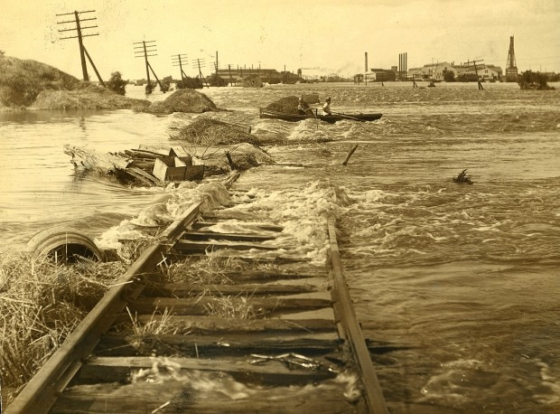 EAST ST. LOUIS FLOOD, 1903  Water rushing over railroad tracks in Madison, Ill., after the Mississippi River broke through the Madison County levees during the 1903 flood. (Missouri History Museum)