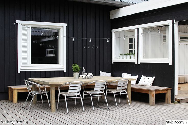 L字型に配置された木製の低いデイベッドのあるウッドデッキの屋外リビング テーブルをおけば屋外ダイニング
