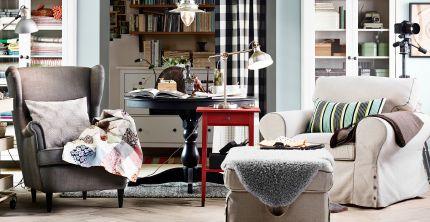 Ruang keluarga dengan dua kursi berlengan IKEA, bangku kaki, meja samping dan rak buku.