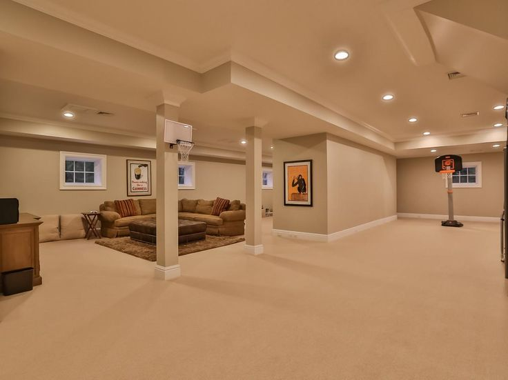 The Spacious Bonus Room Features A Sophisticated Seating Area With Tan Sectional And Leather Ottoman