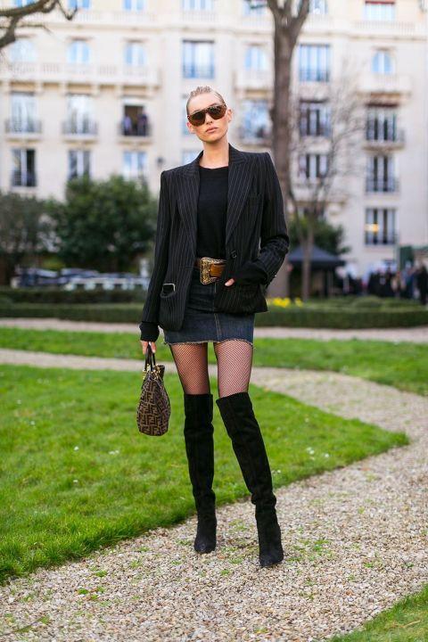 Atrévete a probar la combinación inesperada de blazer elegante y minifalda vaquerajunto a medias y botas mosqueteras.