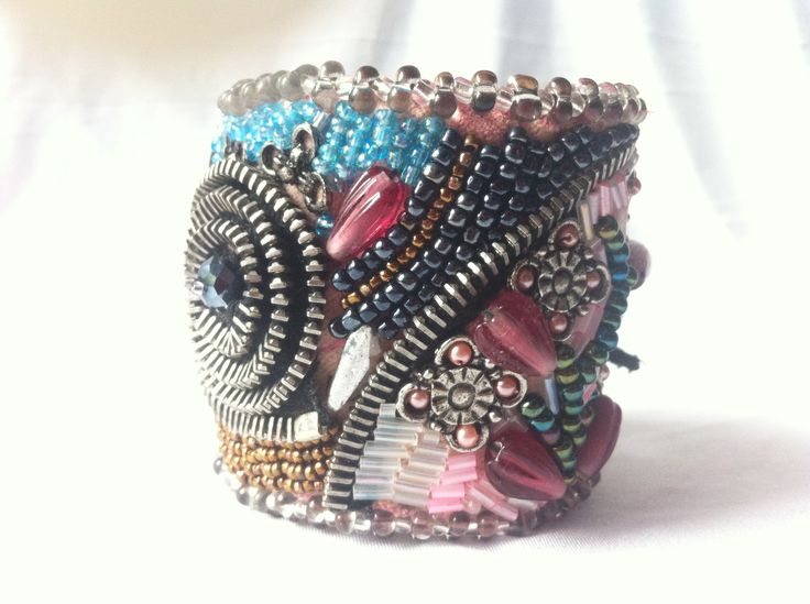 A+big+statement+bracelet+totally+engulfed+in+beads.+It+has+a+big+upcycle+zipper+flower+