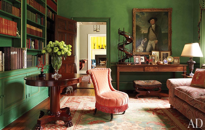 In the library, walls and shelves painted in Benjamin Moore's Van Alen Green and trimmed in gold provide a bold background for antiques.