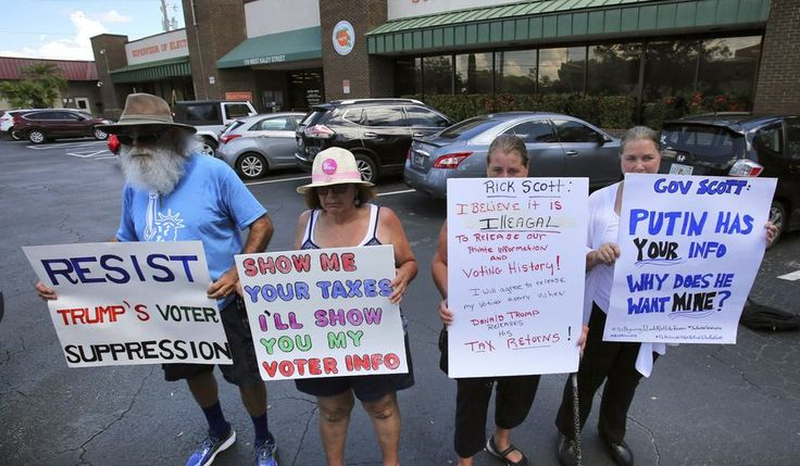 From left, Gary Mogensen, Barbara Ventarola, Carrie Barker-Carson and Karen Louden hold signs as protesters from several central Florida voter advocacy groups demonstrate in front of the Orange County Supervisor of Elections office, in Orlando, Fla., Monday, July 10, 2017. The groups are protesting the support by Florida governor Rick Scott of the voter fraud probe by President Donald Trump that would collect personal voter registration data. (Joe Burbank/Orlando Sentinel via AP)