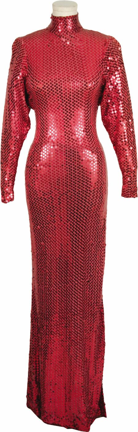 Sonny & Cher Costumes. A Cher cherry red straight-line column dress with applied bright red sequins, a fitted collar, a left leg slit, and a rare Bob Mackie design label