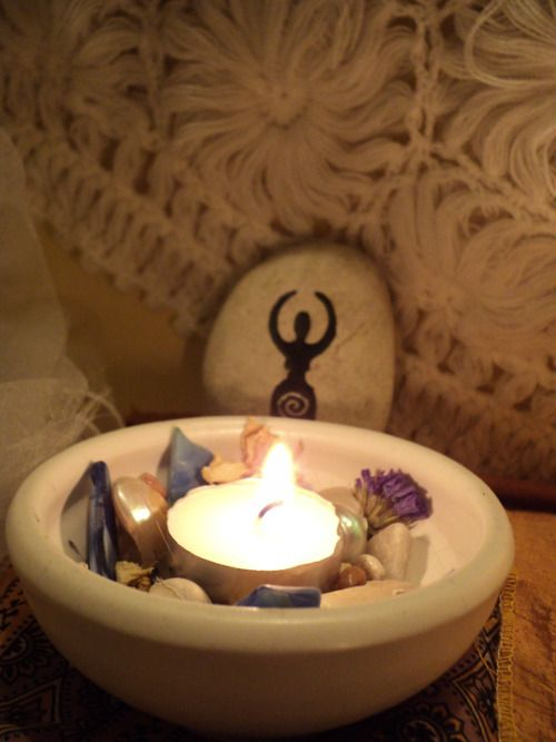 A small dish for the Goddess. Filled with shells, sea glass, white dried flowers, a mirror and a small candle.