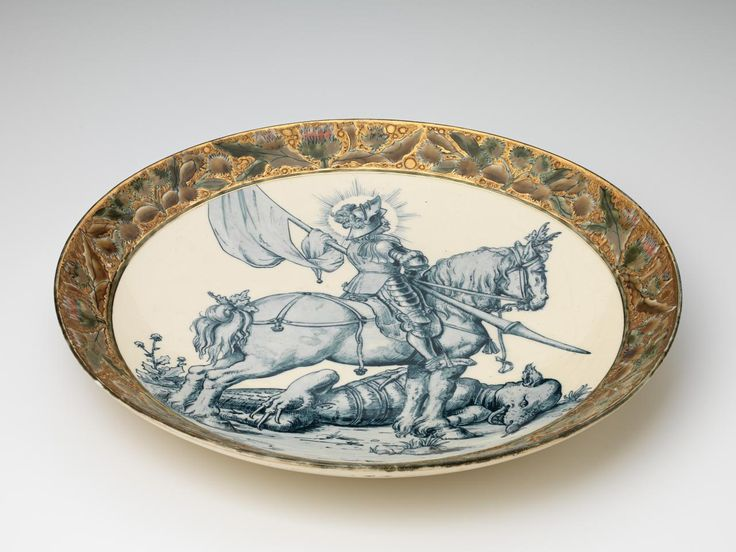 Zsolnay   Saint George and the dragon, plate (c. 1888)  W. ZSOLNAY, Pécs (manufacturer) Keleman KALDEWEY Measurements7.5 × 46.7 cm diameter. Inscriptionpainted in blue on base u.c.: 22 / Zsolnay / Pécs (underlined) (five church steeples) TJM (TJM in a semi-circle) impressed (vertically) in base c. YANLOSZ (NL reversed)