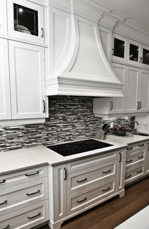 Gorgeous kitchen with crisp white cabinetry, marble countertops and black/grey…