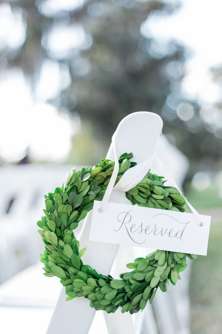 outdoor wedding pew marker is a petite boxwood wreath, tied with a cream satin ribbon.