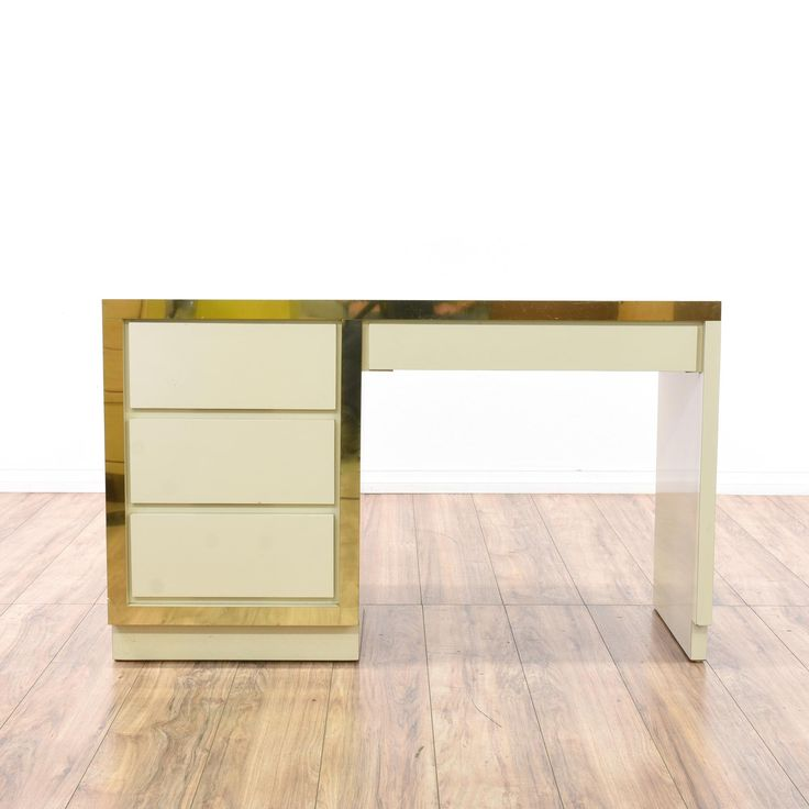 This regency desk is featured in a wood with a glossy white veneer finish. This kneehole desk has 4 drawers, shiny gold trim and a sleek modern design. Perfect for adding a pop of glamour to a space! #bohemian #desks #kneeholedesk #sandiegovintage #vintagefurniture