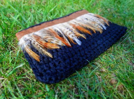 Bolso de mano hecho con trapillo negro, y adornado con plumas de tonos crudos y anaranjados, y cinta de piel marrón en la parte superior.Medidas apro