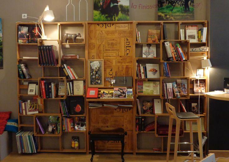 Une bibliothèque conçue à partir des caisses de ce bar à vin reproduites en chêne, le panneau central est composé de couvercles comportant les noms des vins