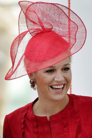 Queen Maxima of The Netherlands in a gauzy red hat that's just the right amount of fun.