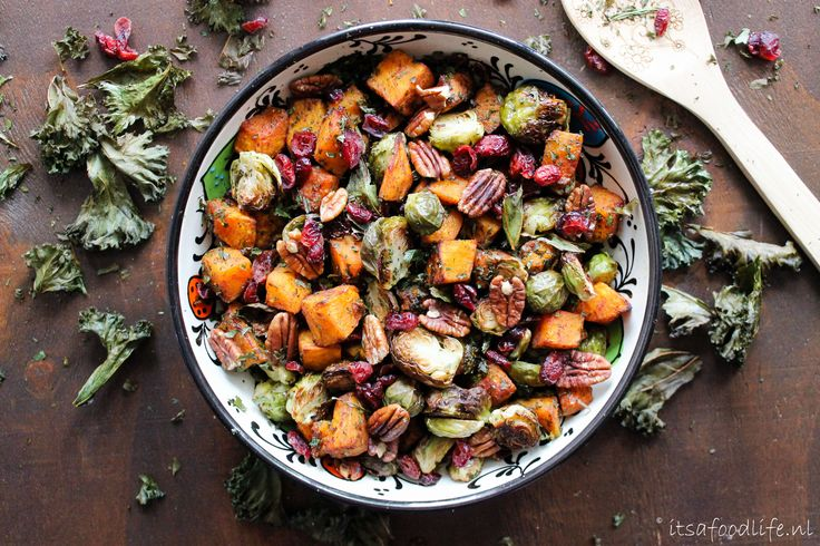 Deze herfstsalade met geroosterde spruitjes en pompoen met peccannoten, cranberries en boerenkool chips is een prima kameraad op een gure koude herfstavond.