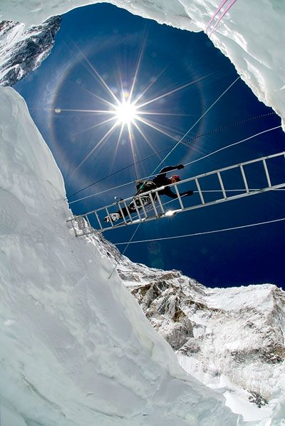 Crossing a crevasse in the Khumbu Icefall, 5,486 metres (17,999 ft) on the Nepali slopes of Mount Everest not far above Base Camp and southwest of the summit. The icefall is regarded as one of the most dangerous stages of the South Col route to Everest's summit.