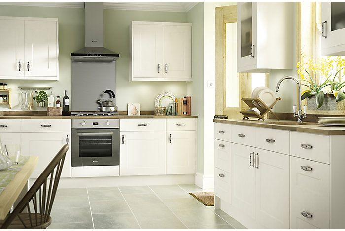 Cream shaker with wooden tops, more of a grey ceramic floor. Pale green feature wall?