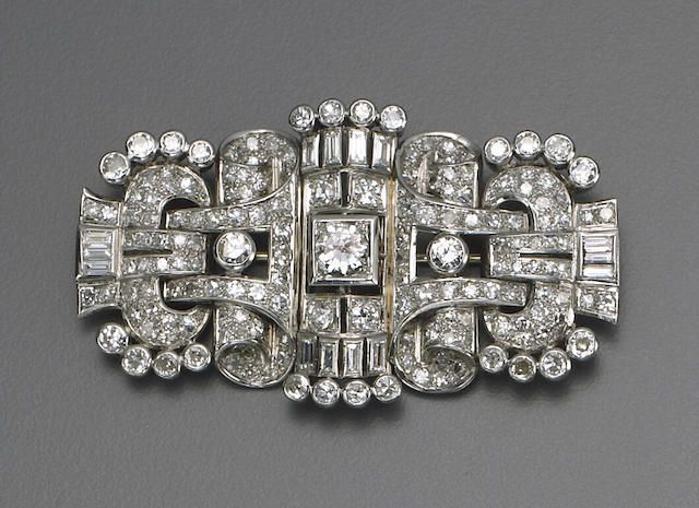 An art deco diamond and platinum brooch, circa 1930 the openwork shaped-rectangular panel centering a transitional-cut diamond within a square-shaped collet, pavé-set throughout with old European-cut diamonds, baguette-cut diamonds at the four points and detailed on the edges with old European-cut diamond collets; width: 2½in; estimated total diamond weight: 10.00 carats.