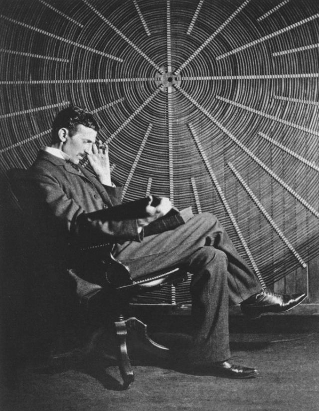 "Nikola Tesla, with Roger Boskovich's book, ""Theoria Philosophiae Naturalis,"" in front of the spiral coil of his high-frequency transformer at East Houston St. 46, New York."