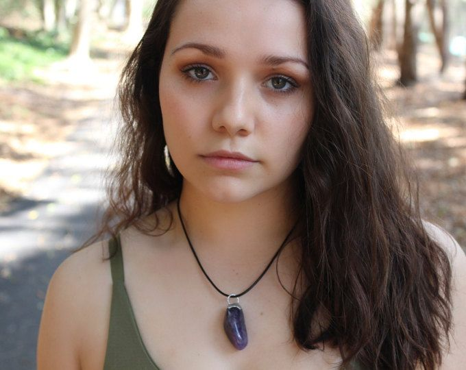 The beautiful Amethyst, known to calm and ground the wearer while providing aid to eliminate impatience, is stunning in its smooth, tumbled form. This beauty is available with a silver chain, or worn short with a black choker.