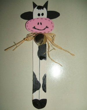 A whimsical cow bookmark in black and white and pink with a rustic bow.. made from a large craft stick.