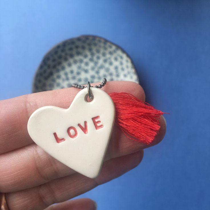 Collana lunga con catenella bronzo con nappina rossa e ciondolo in argilla a forma di cuore bianco con incisa