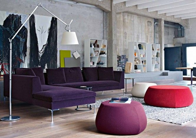 The red and purple passion spills out into the lounge area by way of an oversized L-shaped grape sofa and funky footstools.
