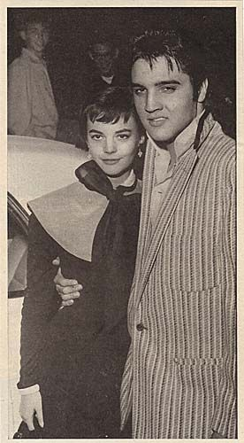 """Elvis Presley standing with his arm around a young Natalie Wood in front of what looks to be a car. Natalie had come to Memphis as a house guest of the parents of Elvis and was treated to a ride in Elvis's White Continental Mark II and on his motorcycle. It seems to have been a relationship where there may have been sparks but there was no fuel. Elvis was quoted as saying """"I'd be crazy to get married now. I like to play the field"""". 1956"""