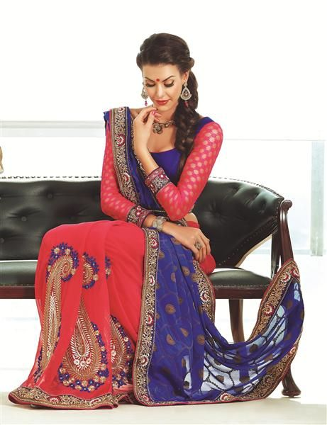 """This saree is purely made keeping in mind this festive season.This saree Doesnt impact on the latest trend but has a simple an sober look depicting """"Fashion alongwith Tradition """". The red skirt of the saree comprises on fanatic designs made up of """"Zari work , blue and gold threads """"one goes alongwith the pallu and one goes contrast to the skirt colour. *Blouse included(unstiched)."""