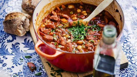 Fräs rödlök och vitlök i en stor kastrull i olivolja på medelvärme. Skär morötter, blekselleri och salsiccia i bitar, lägg i kastrullen. Salta, peppra och krydda med paprikapulvret. Fräs grönsakerna i 3–4 minuter och tillsätt vinet, låt koka ihop i ett par minuter och lägg sedan i krossade tomater, linser och bönor. Låt puttra ca 10 minuter. Toppa stufaton med persilja och ringla över Novello precis före servering. Bjud gärna ett gott bröd till.