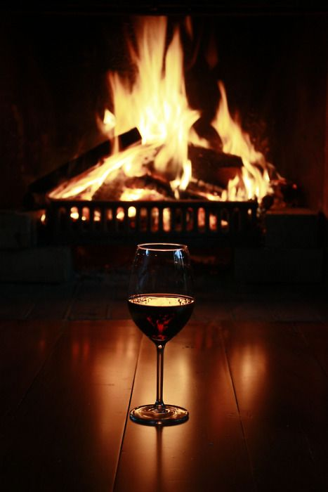 a glass of wine in front of a crackling fire.