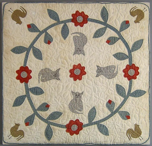 """Applique crib quilt, ca. 1900, with central floral wreath and cats and roosters, 32 1/2"""" x 34"""". Provenance: Ex-Collection of Betty Mintz."""