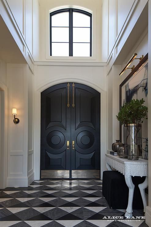 A two story foyer features black arched front doors accented with brass plates alongside a large art piece illuminated by a brass picture light over a Noir Pegas Console, atop a black and white diamond pattern floor in First Snow Elegance Marble, Zebrano Marble and Absolute Black Granite.