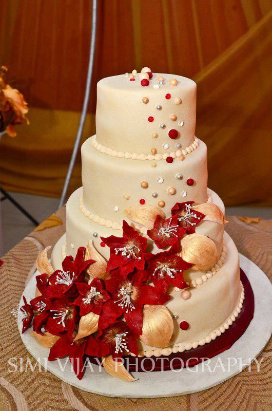 Round Wedding Cakes - Fruit cake with fondant flowers and hand rolled balls dusted with lustre dust, edible gems, large silver dragees. Airbrushed with pearl sheen. This design is copied from RATGA (Buttercream Lilly Cascade- found on cakecentral) so the design isnt mine.