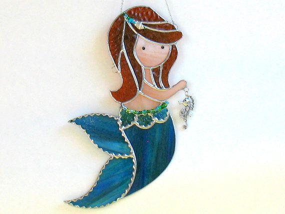 Deze grote zeemeermin in gebrandschilderd glas zou maken het perfecte cadeau voor een strand liefhebber of verzamelaar van de zeemeermin.  Ze is een zeer aanzienlijke omvang van 12 lang en 6 1/2 brede op haar breedste deel, en haar staart is gemaakt van een mooi stuk van aqua (blauw/groen) glas. Ze is een roodharige, net als de zeemeermin in het verhaal The Little Mermaid. In haar hand houdt zij een mooie filigreed seahorse en haar taille en de haren zijn versierd met glaskralen en ...