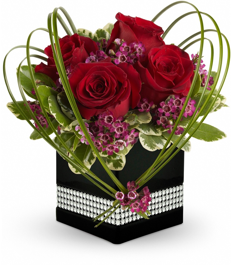"Sweet Thoughts - A deluxe mix of red roses and purple waxflower - accented with bear grass and greenery - is delivered in a ceramic planter with diamonds Cube vase. Approximately 9 1/2"" W x 11"" H"
